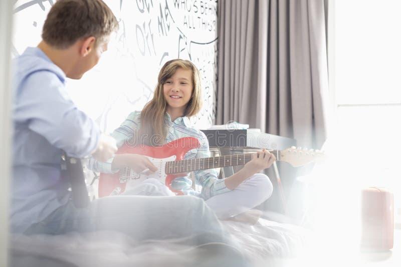 Muchacha con el padre que toca las guitarras eléctricas en casa imagen de archivo