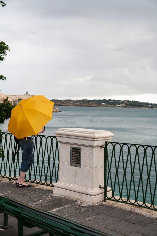 Muchacha con el paraguas amarillo imagenes de archivo