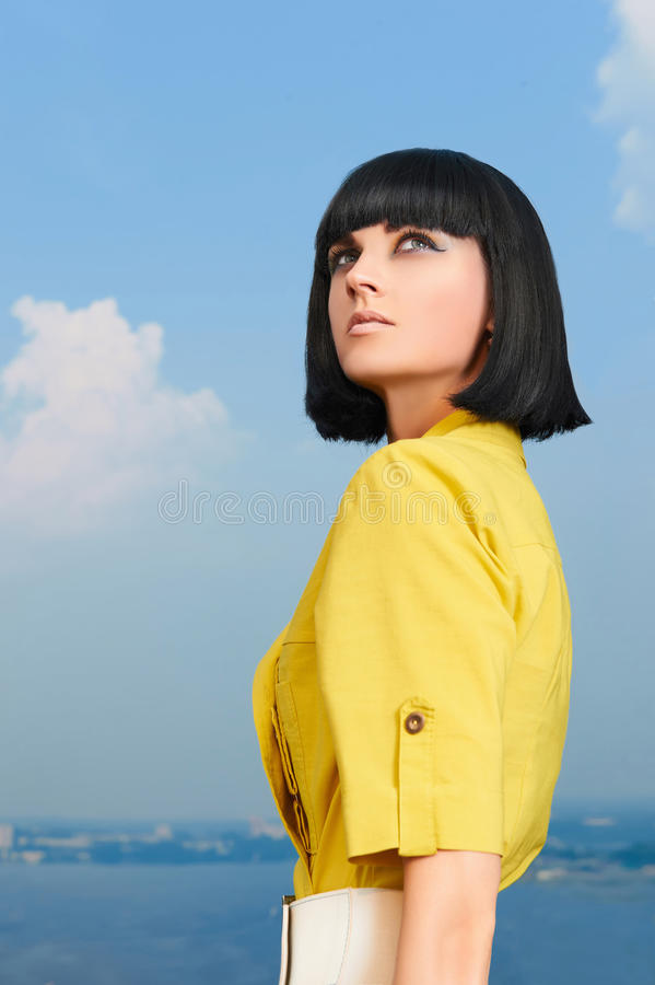 Muchacha con el peinado de la sacudida sobre el cielo azul fotos de archivo