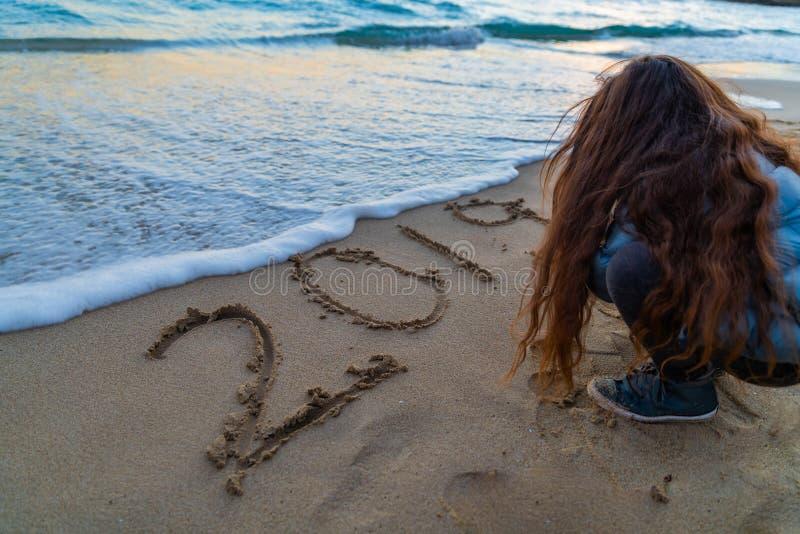 Muchacha con el pelo largo que escribe 2019 en la playa fotografía de archivo libre de regalías