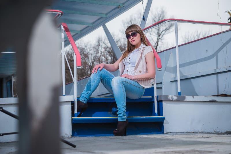 Muchacha con el pelo ligero que se sienta en las escaleras, primavera, día caliente soleado, en gafas de sol y tejanos reclinació imagenes de archivo