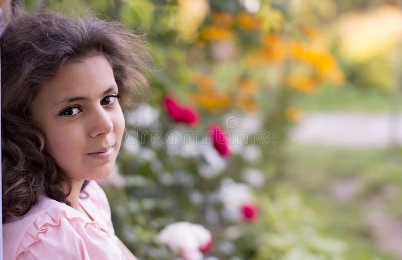 Muchacha con el pelo oscuro que se sienta en el umbral en el jardín imagen de archivo libre de regalías
