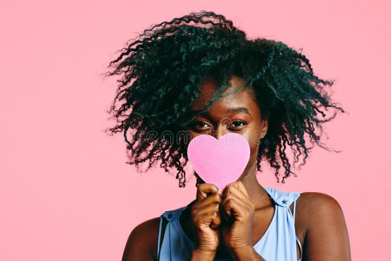 Muchacha con el pelo rizado negro azulado que lleva a cabo un corazón rosado delante de su cara fotografía de archivo