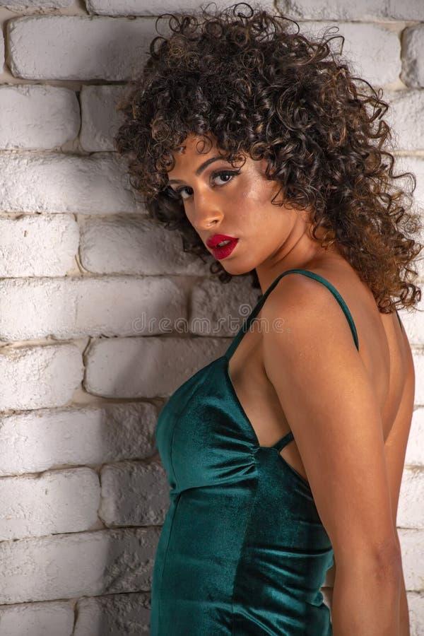 Muchacha con el pelo rizado negro largo y maquillaje en un vestido de noche verde en un fondo de la pared de ladrillo blanca fotografía de archivo