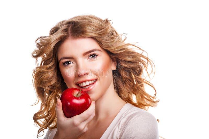 Muchacha con el pelo rizado que celebra una manzana y una sonrisa rojas imagen de archivo