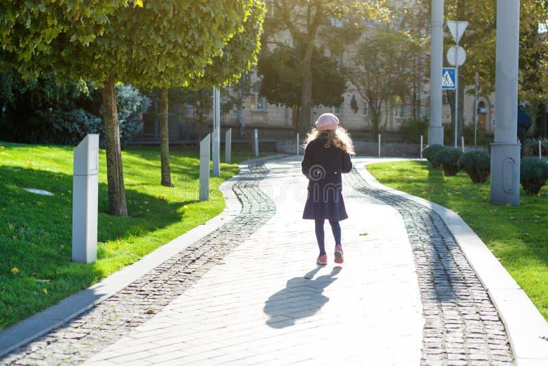 Muchacha con el pelo rizado rubio largo en capa azul marino y boina francesa foto de archivo