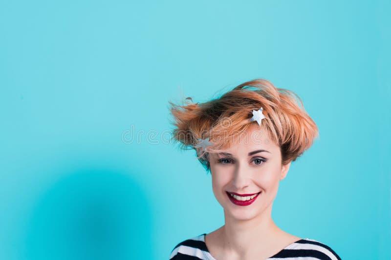Muchacha con el pelo rojo que ríe llevando a cabo su cabeza Pelo enredado Emociones positivas Tiro del estudio fotografía de archivo