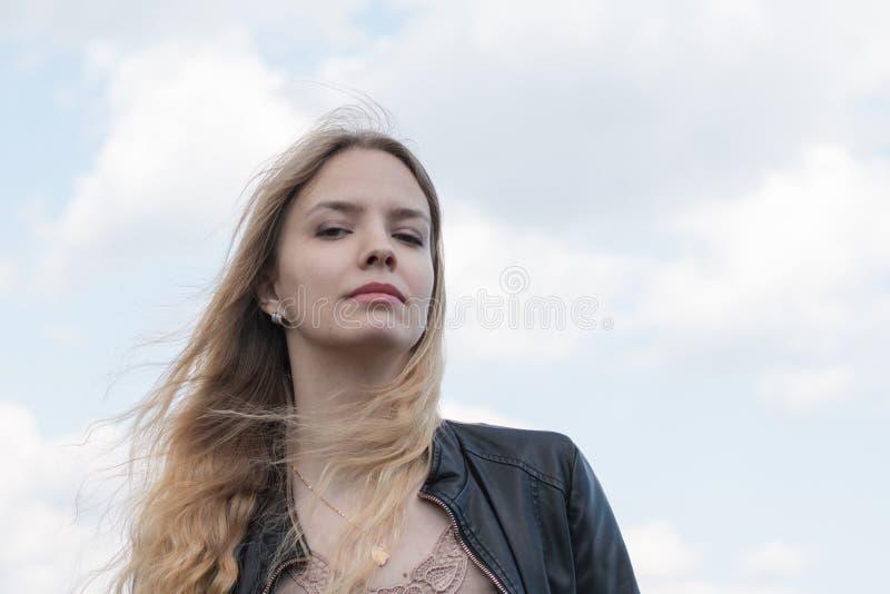 Muchacha con el pelo rubio y la nube azul del cielo y blanca fotos de archivo libres de regalías