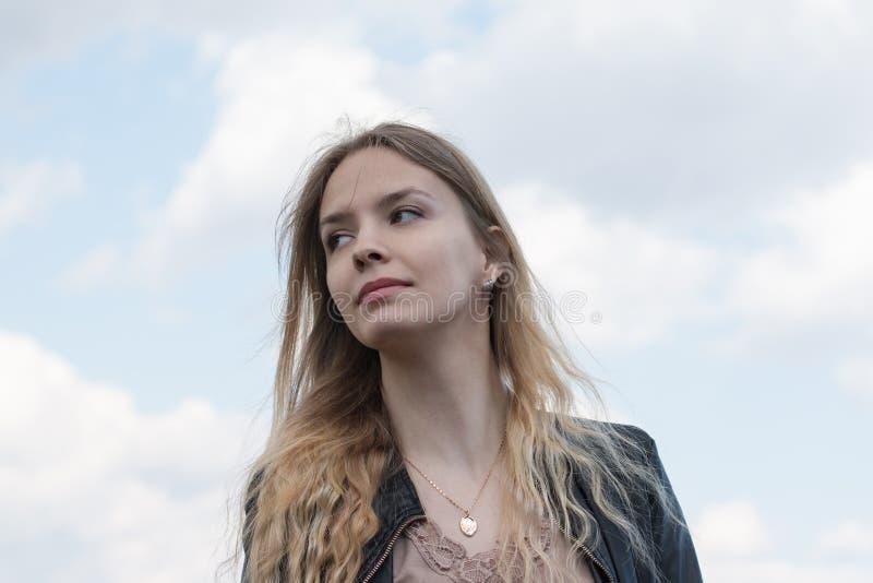 Muchacha con el pelo rubio y la nube azul del cielo y blanca foto de archivo