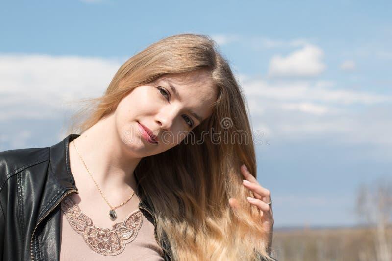 Muchacha con el pelo rubio y la nube azul del cielo y blanca fotos de archivo