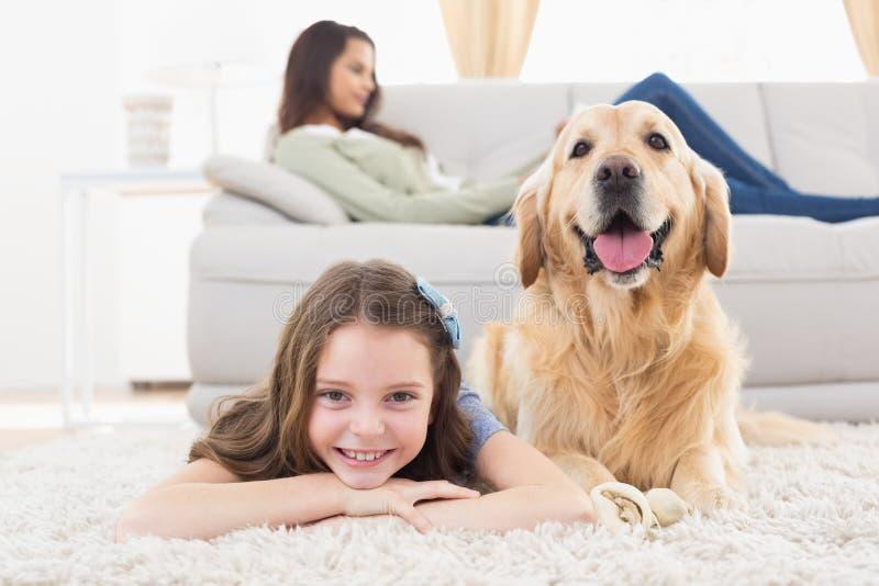 Muchacha con el perro que miente en la manta en casa fotos de archivo libres de regalías