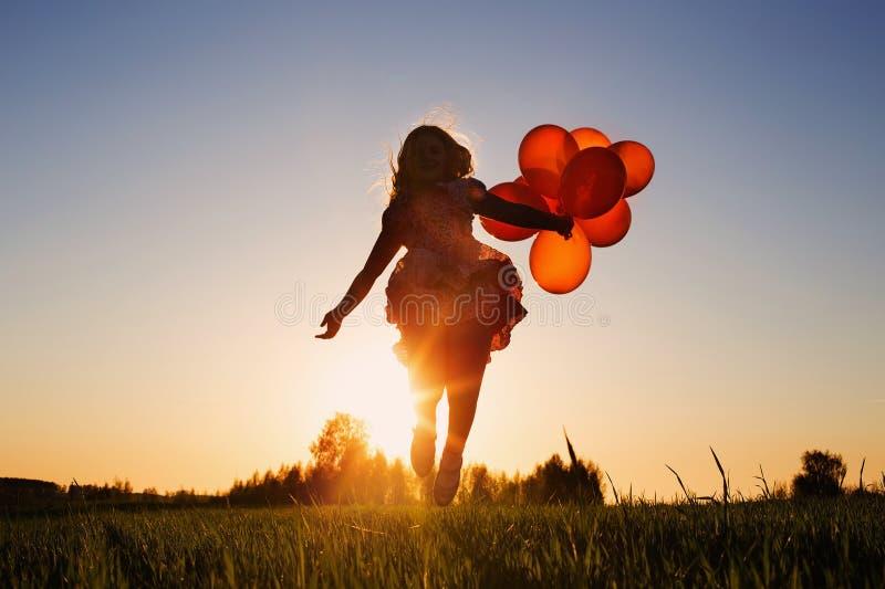 Muchacha con el salto de los globos fotos de archivo libres de regalías