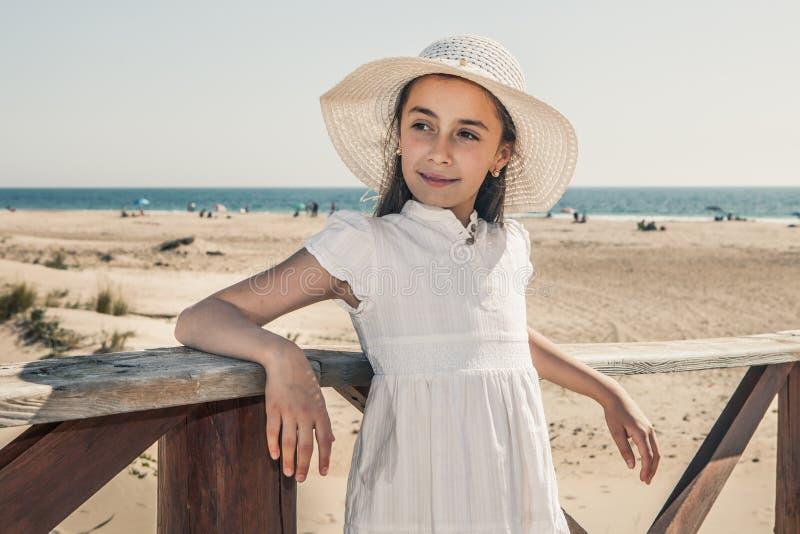 Muchacha con el sombrero blanco que descansa sobre una verja de madera en la playa imagenes de archivo