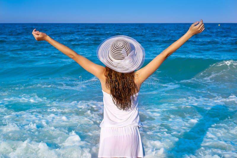 Muchacha con el sombrero de la playa en brazos abiertos del mar fotografía de archivo