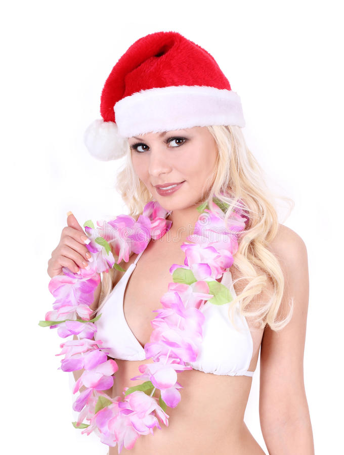 Muchacha con el sombrero de Santa y los accesorios hawaianos fotos de archivo