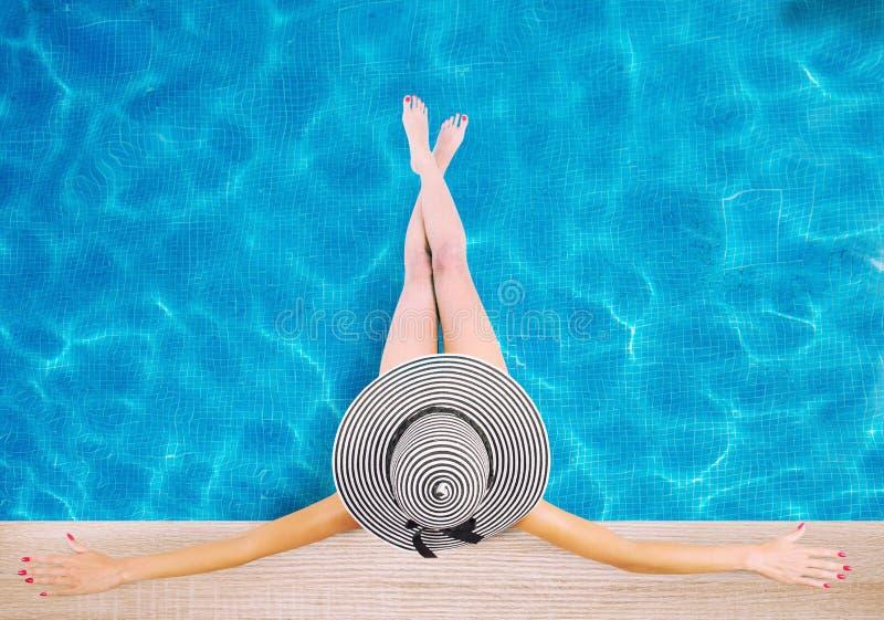 Muchacha con el sombrero en la piscina El concepto de verano se relaja fotos de archivo