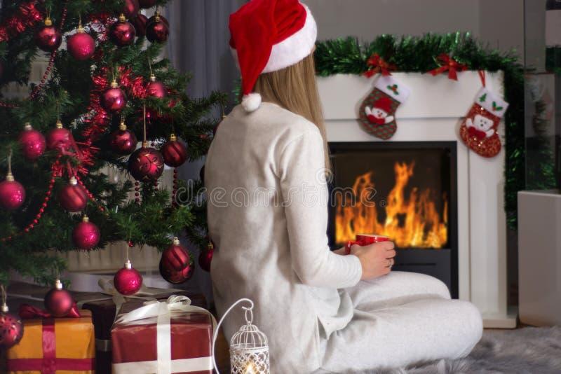 Muchacha con el sombrero rojo y el pijama que se sientan cerca de la chimenea adornada imagen de archivo libre de regalías