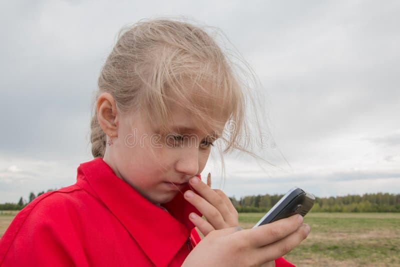 Muchacha con el teléfono celular y el cielo nublado foto de archivo