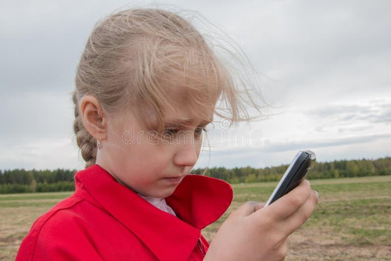 Muchacha con el teléfono celular y el cielo nublado imagen de archivo libre de regalías