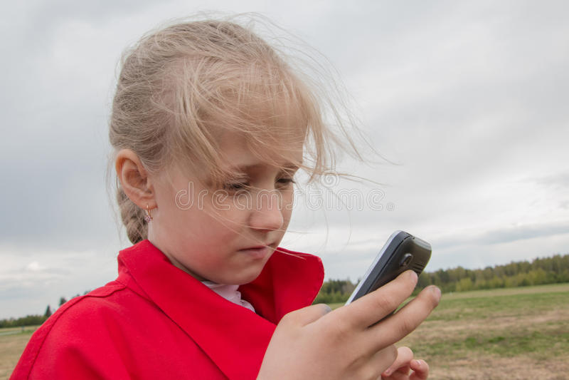 Muchacha con el teléfono celular y el cielo nublado imagen de archivo