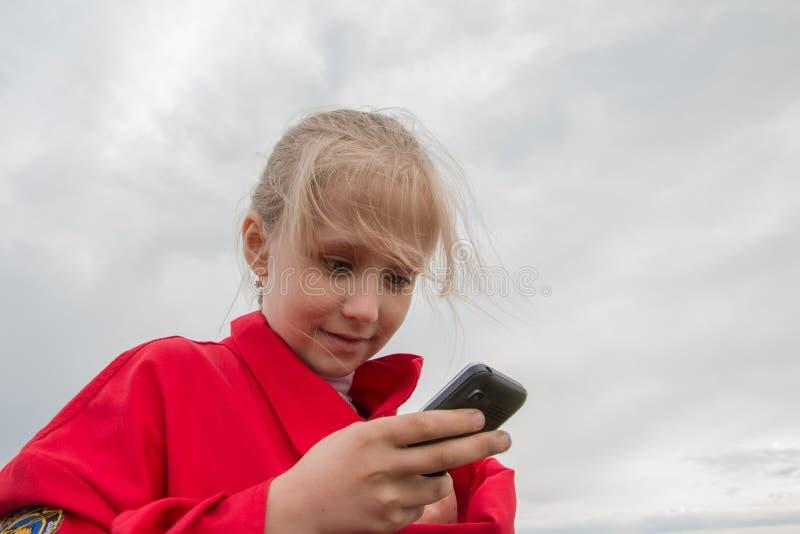 Muchacha con el teléfono celular y el cielo nublado fotos de archivo