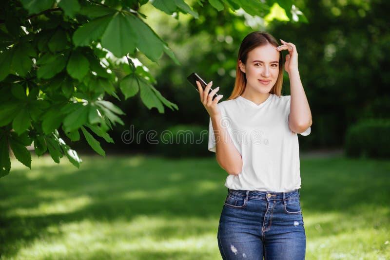 Muchacha con el teléfono en parque imagenes de archivo