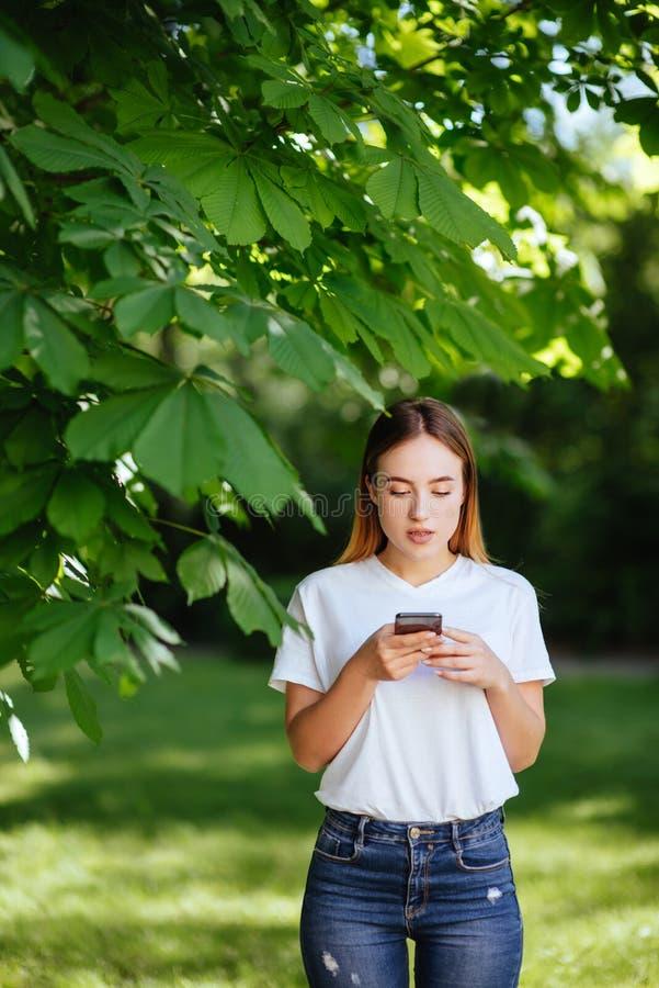 Muchacha con el teléfono en parque fotografía de archivo