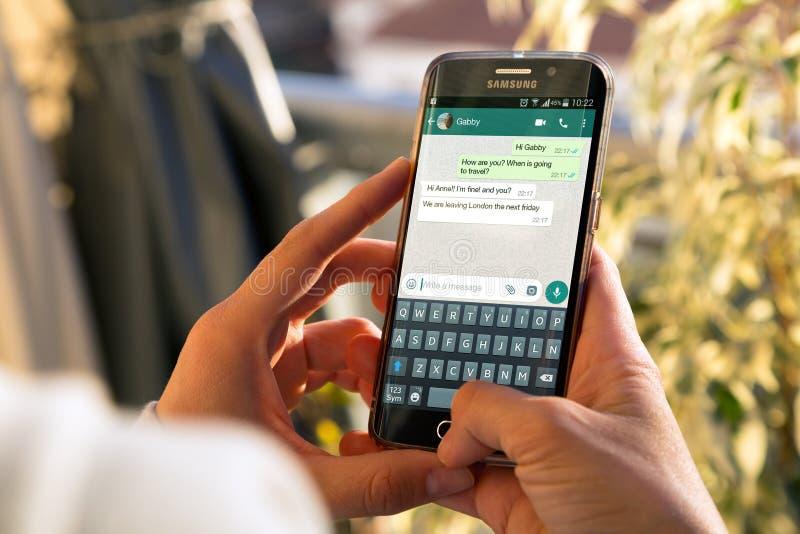 Muchacha con el tel?fono en sus manos y una conversaci?n del whatsapp sobre la pantalla foto de archivo