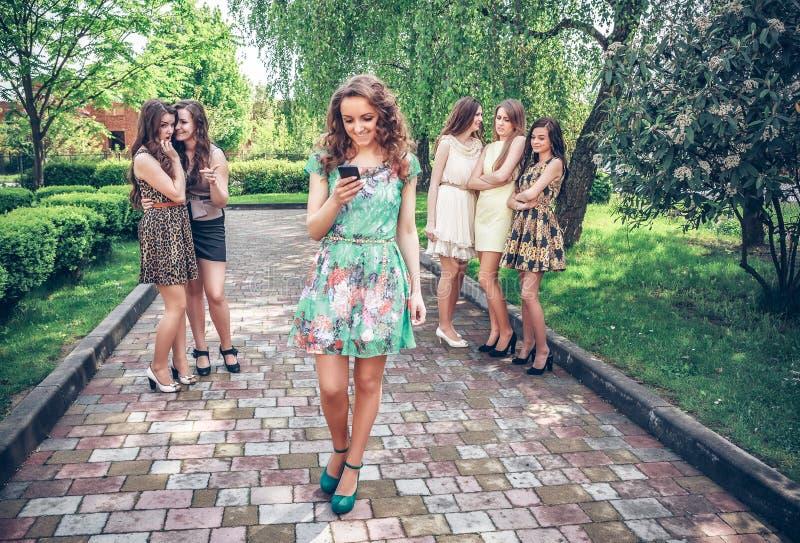 Muchacha con el teléfono móvil y grupo de envidiar a muchachas imágenes de archivo libres de regalías