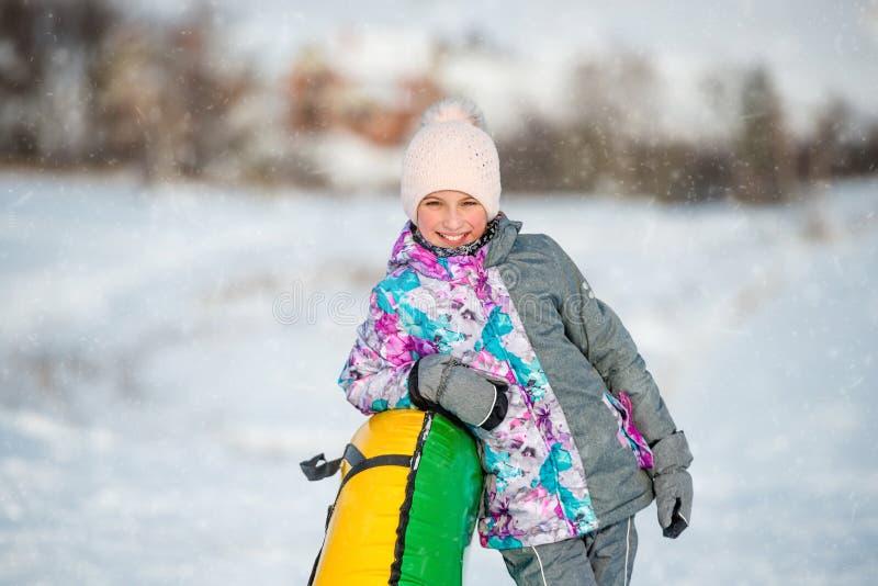 Muchacha con el trineo inflable de la nieve encendido cuesta abajo en el invierno imágenes de archivo libres de regalías