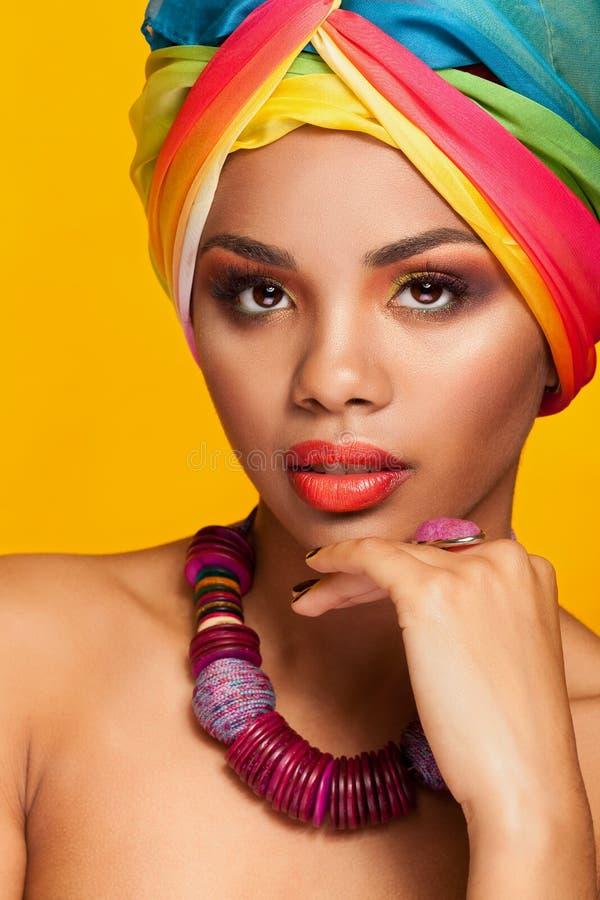 Muchacha con el turbante étnico afroamericano en fondo amarillo foto de archivo libre de regalías