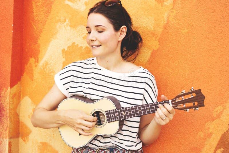 Muchacha con el ukelele de la guitarra en el fondo de la pared imagenes de archivo