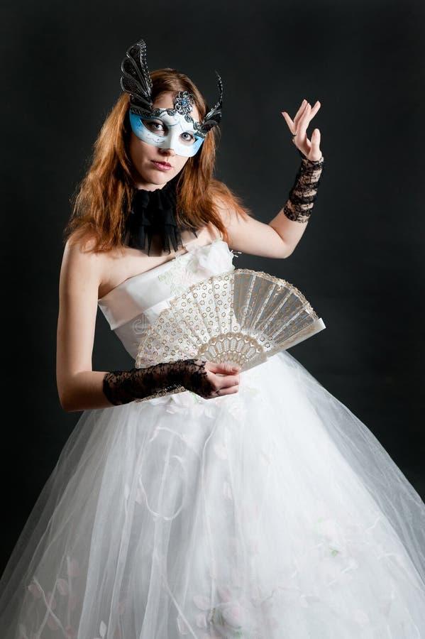 Muchacha con el ventilador y máscara en la alineada blanca imagen de archivo
