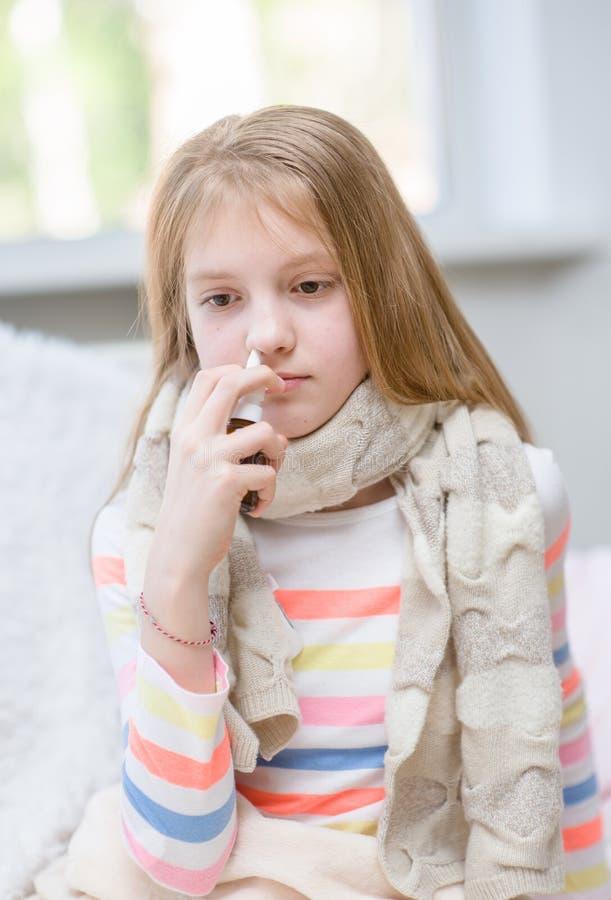 Muchacha con gripe usando el espray de nariz imagen de archivo