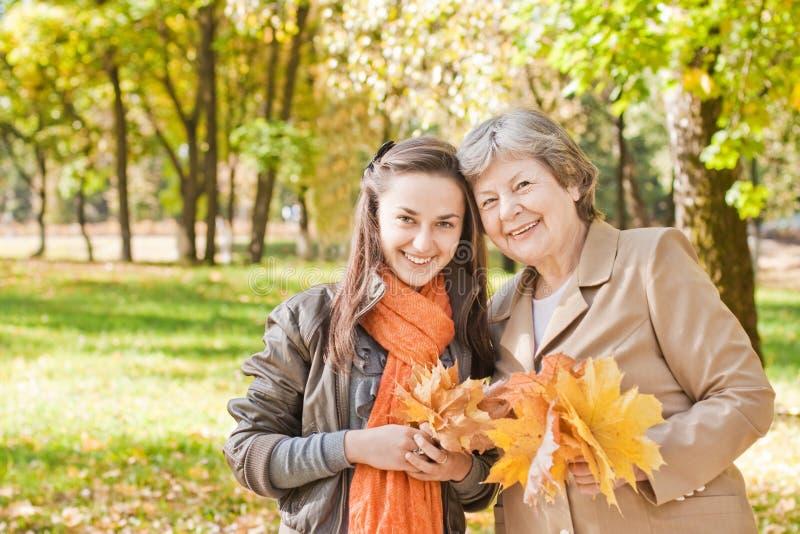 Muchacha con la abuela en parque del otoño fotografía de archivo