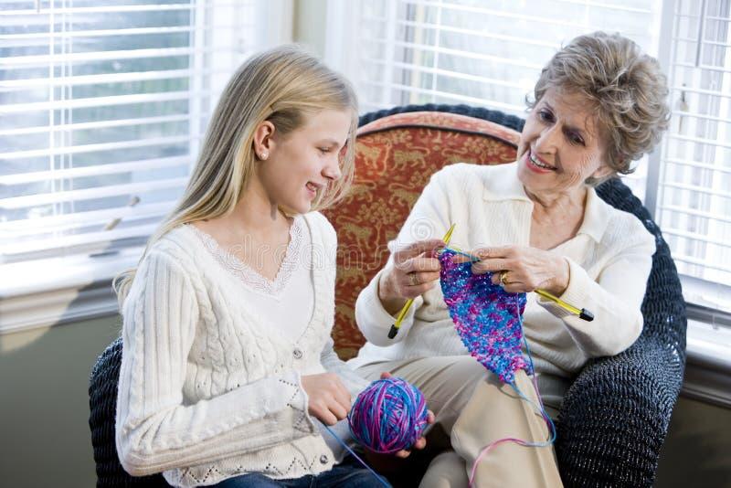Muchacha con la abuela que hace punto en sitio cariñoso foto de archivo