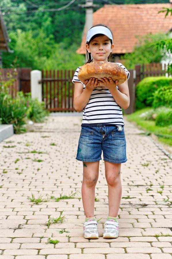 Muchacha con la barra de pan fotografía de archivo