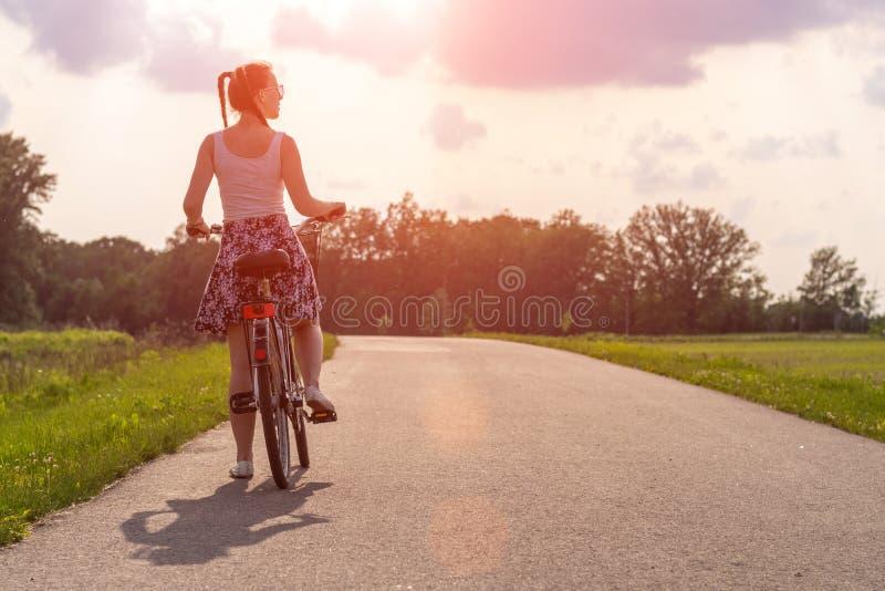 Muchacha con la bici en la puesta del sol del verano en el camino en el parque de la ciudad Rueda del primer del ciclo en fondo b imágenes de archivo libres de regalías