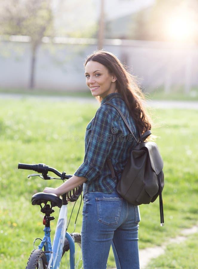 Muchacha con la bicicleta en prado imágenes de archivo libres de regalías