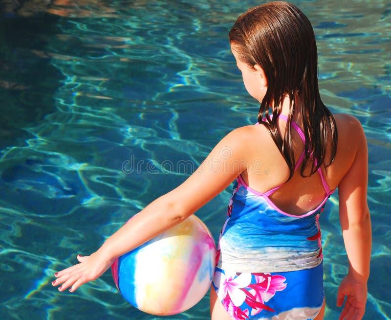 Muchacha con la bola por la piscina fotografía de archivo libre de regalías