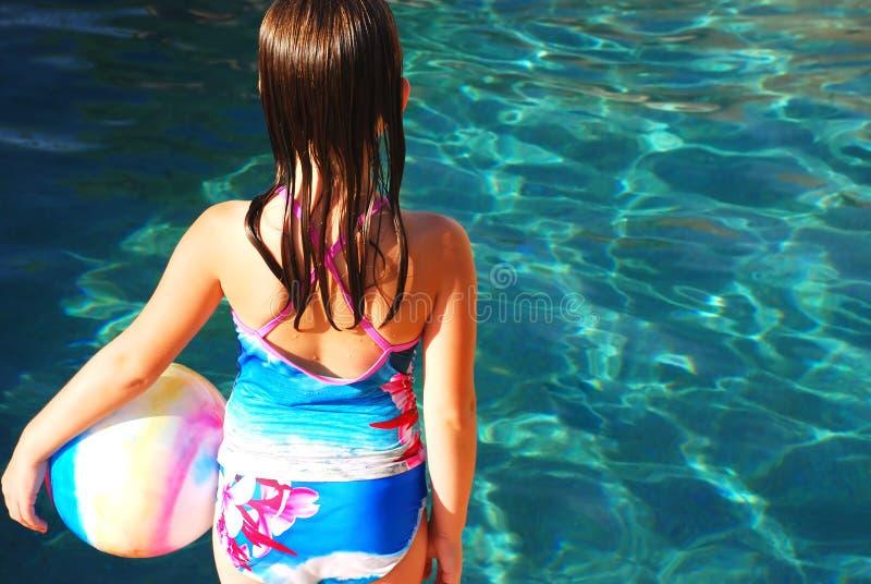 Muchacha con la bola por la piscina imágenes de archivo libres de regalías