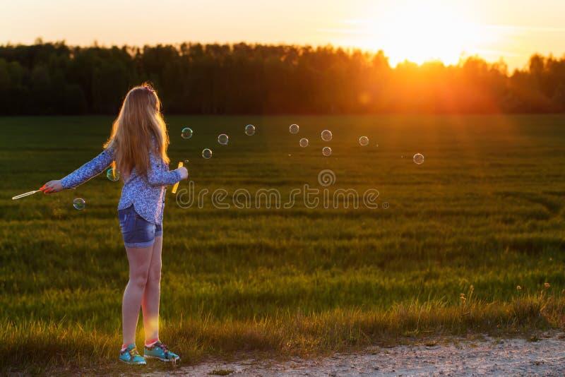 muchacha con la burbuja de jabón al aire libre foto de archivo