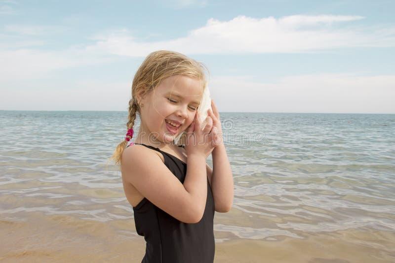 Muchacha con la cáscara que escucha el mar fotografía de archivo libre de regalías