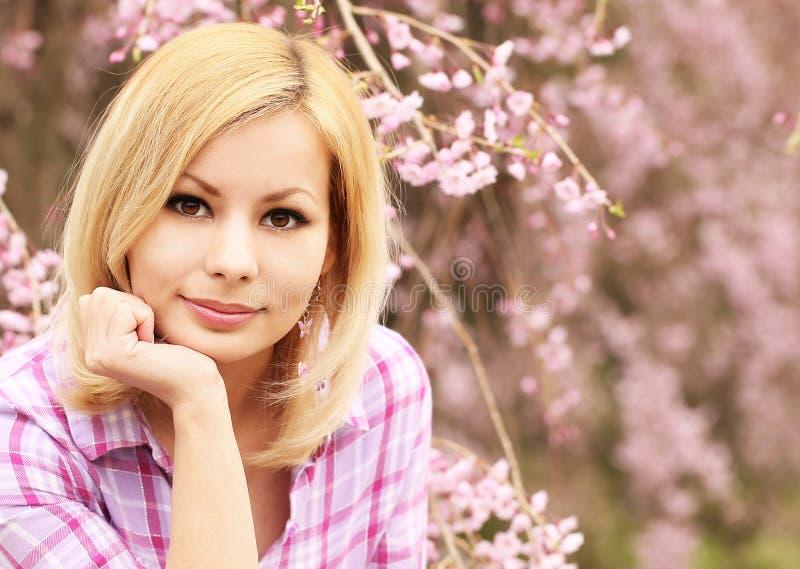 Muchacha con la flor de cerezo Mujer joven rubia hermosa fotografía de archivo libre de regalías