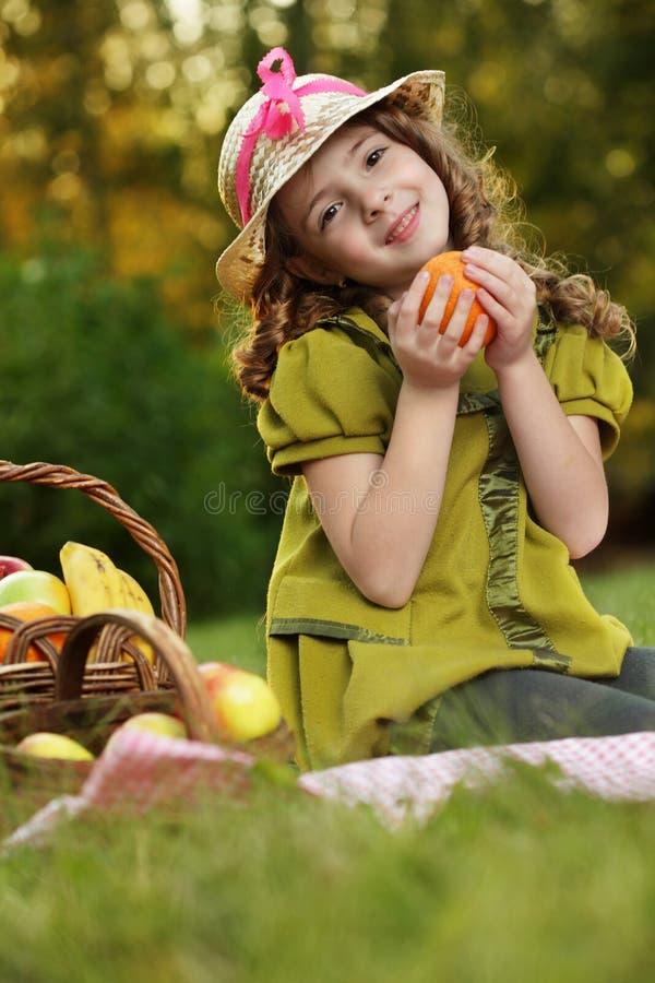Muchacha con la fruta anaranjada foto de archivo
