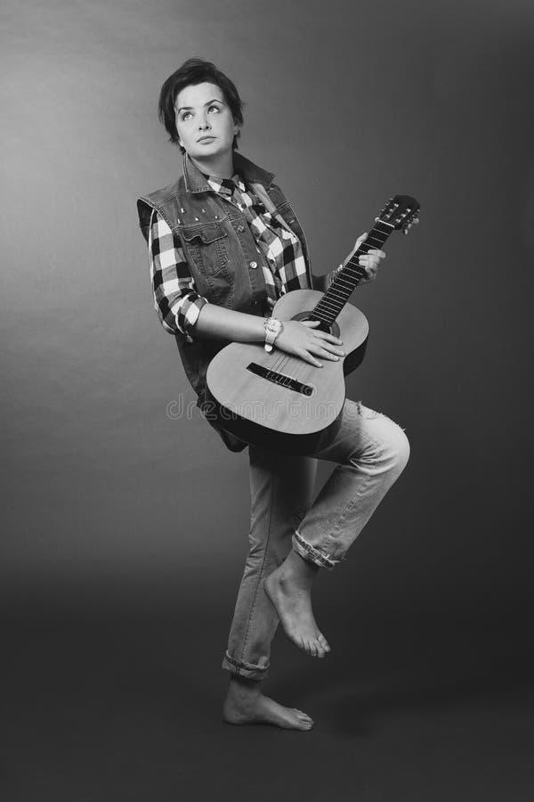 Muchacha con la guitarra blanco y negro descalzo en vaqueros fotografía de archivo libre de regalías