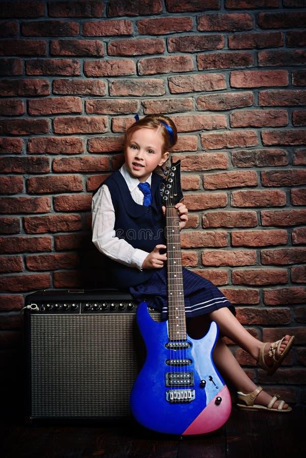 Muchacha con la guitarra eléctrica imagenes de archivo