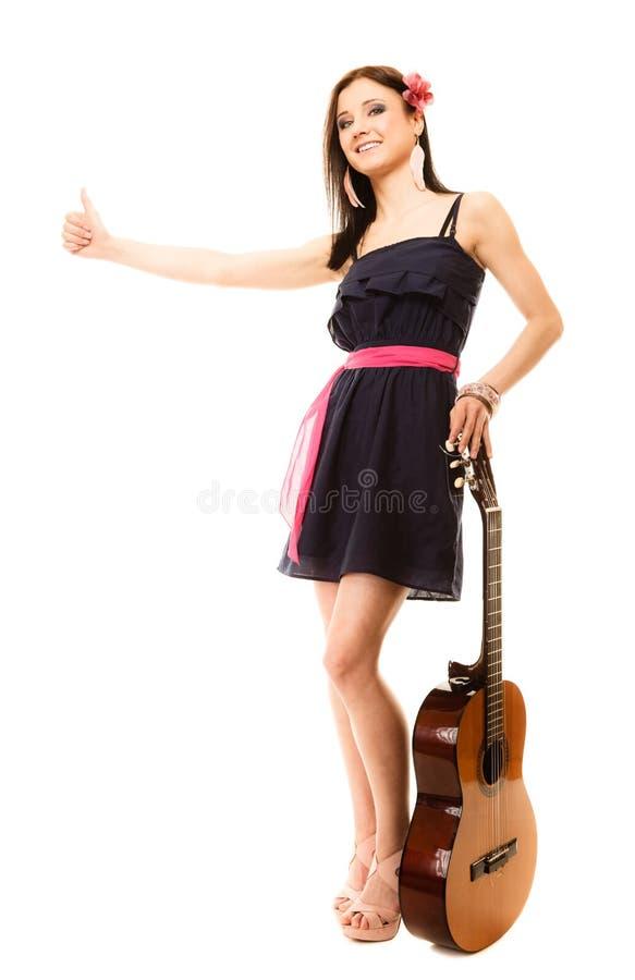 Muchacha con la guitarra que manosea con los dedos y el caminar del tirón aislada imagen de archivo