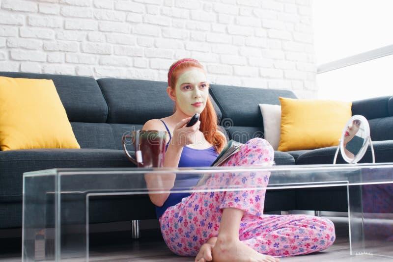 Muchacha con la lectura de la máscara de la belleza y la televisión de observación en casa imagenes de archivo