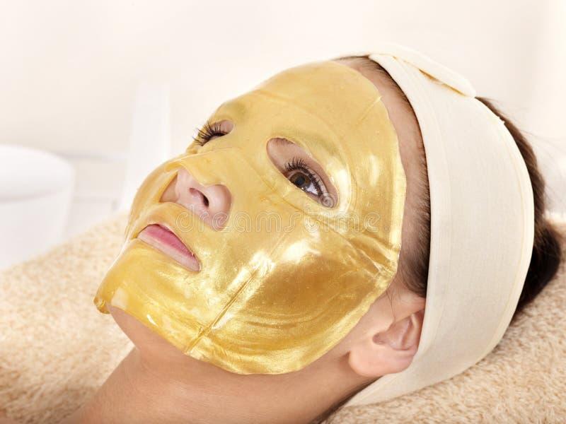 Muchacha con la máscara del facial del oro. foto de archivo